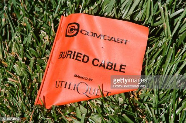Utility marking flag indicating the position of a buried communications cable for Comcast Corporation placed by the utility damage prevention company...