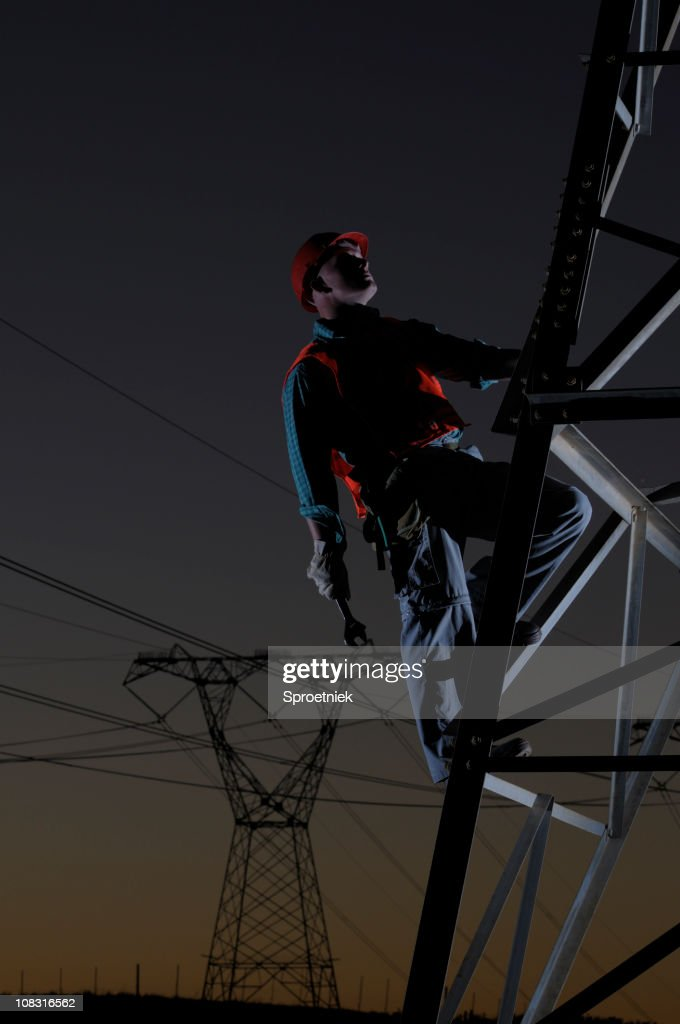 Utility worker against power pylons at dusk : Stock Photo