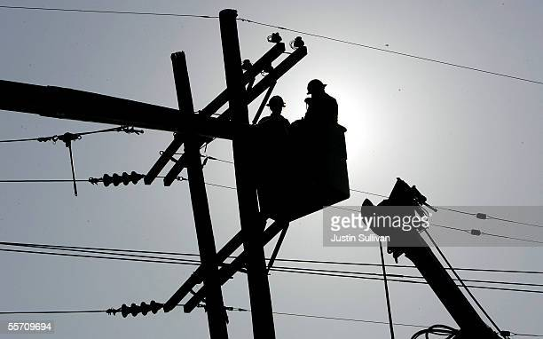 Utility workers repair a power line September 17 2005 in the Lower Ninth Ward of New Orleans Louisiana Rescue efforts and clean up continue in the...
