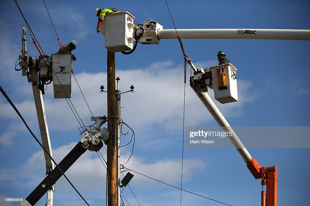 Utility workers replace a pole that was damaged by Superstorm Sandy on November 25, 2012 in Seaside Heights, New Jersey. New Jersey Gov. Christie estimated that Superstorm Sandy cost New Jersey $29.4 billion in damage and economic losses.