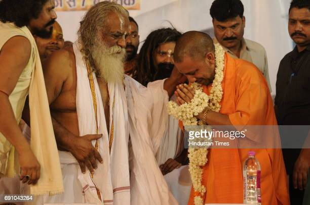 Uttar Pradesh Chief Minister Yogi Adityanath bows to Mahant Nritya Gopal Das during his 79th birthday function on May 31 2017 in Ayodhya India On his...