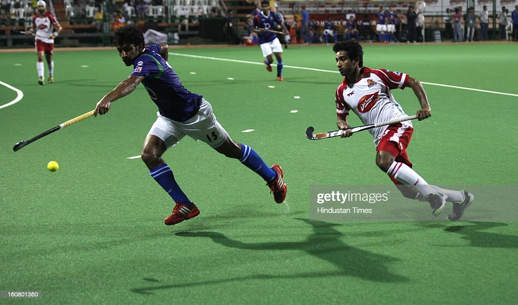 Uttar Pradesh Wizards player Uthappa Sannuvanda (L) and Mumbai Magicians player fight for the possession of the ball during their Hockey India League match at BHA on February 5, 2013 in Mumbai, India.
