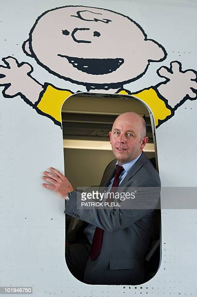 Uwe Balser chairman of German airline Condor poses in the door of an airplane decorated with protagonists of the US comic strip 'Peanuts' on June 10...
