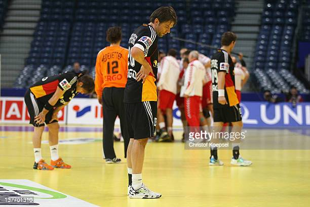 Uwe Gensheimer Christian Sprenger and Martin Strobel of Germany look dejected after losing 3233 the Men's European Handball Championship second round...