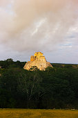 Uxmal, Yucatan, Mexico: Sunlit Pyramid of the Magician (surrounded by  jungle) shot from a distance at dusk. Uxmal is a UNESCO World Heritage site 60 kilometers south of Merida.