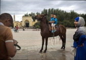 Uyghur boys sit on top of a horse to have their picture taken in front of the Id Kah Mosque China's largest mosque on July 31 2014 in Kashgar...