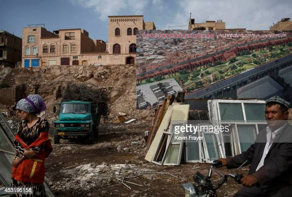 Uyghur labourers stand in front of a map of the plans for development of old Kashgar where traditional homes have been demolished by local...