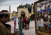 Uyghur man and his son look as photos as women stand in front of the Id Kah Mosque China's largest on July 31 2014 in Kashgar Xinjiang Uyghur...