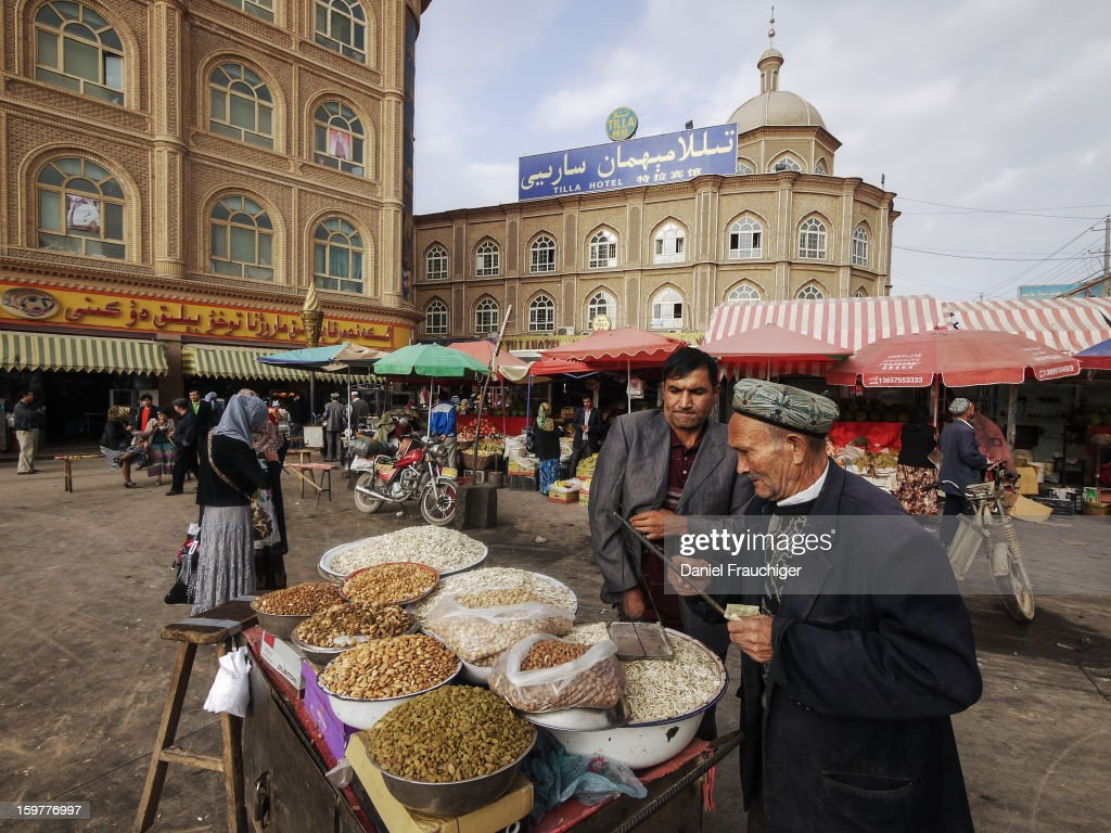 CONTENT] Uyghur market vendor selling seeds and nuts on the market square. In Kashgar, Xinjiang, China. September 16, 2011.