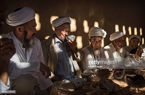 Uyghur men gather for a holiday meal during the Corban Festival on September 13 2016 in Turpan County in the far western Xinjiang province China The...