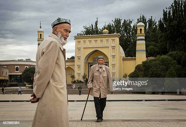Uyghur men walk in front of the Id Kah Mosque China's largest mosque on July 31 2014 in Kashgar Xinjiang Uyghur Autonomous Region China The imam of...