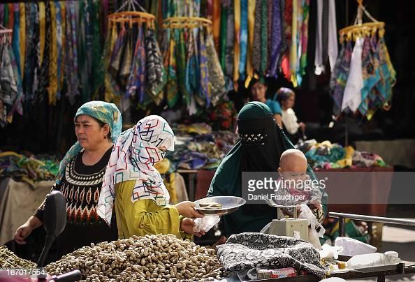 CONTENT] TURPAN CHINA SEPTEMBER 14 2011 Uyghur muslim women trading food at the Turpan city market on September 14 2011 in Turpan China