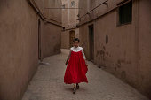 Uyghur woman wearing a gown for the Eid holiday walks from her house on July 30 2014 in old Kashgar Xinjiang Uyghur Autonomous Region China Nearly...