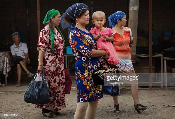 Uyghur women stand in a market while shopping before the Corban Festival on September 10 2016 in Turpan County in the far western Xinjiang province...