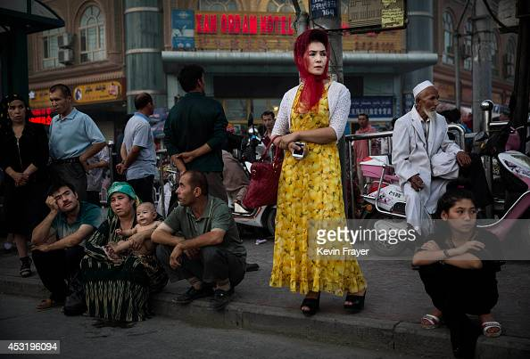 Uyghurs wait at a bus stop on July 27 2014 in old Kashgar Xinjiang Uyghur Autonomous Region China Nearly 100 people have been killed in unrest in the...