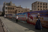 Uyghurs walks passed a construction site for a new building project to replace old homes demolished in recent years on August 2 2014 in Kashgar...