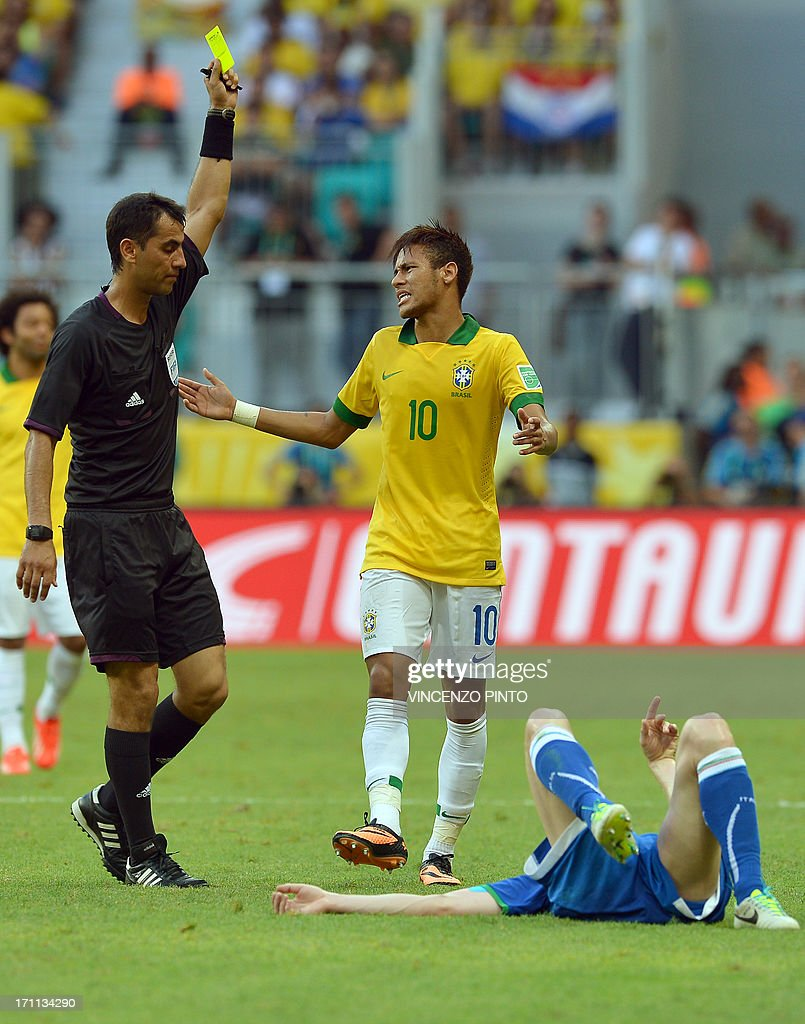 Uzbek referee Ravshan Irmatov (L) shows the yellow card to Brazil's forward Neymar (C) after a foul on Italy's defender Ignazio Abate, during their FIFA Confederations Cup Brazil 2013 Group A football match, at the Fonte Nova Arena in Salvador, on June 22, 2013.