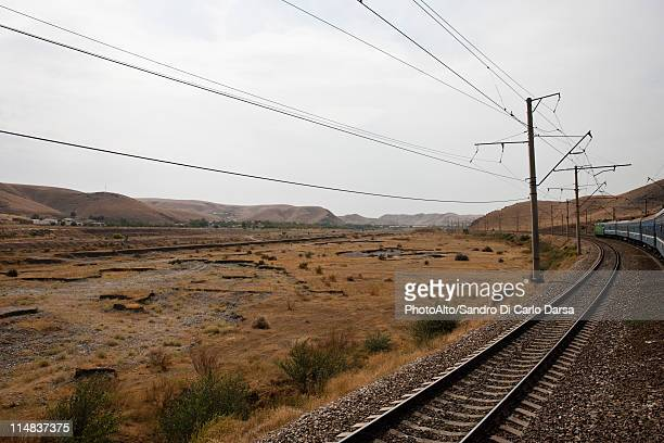 Uzbekistan, Bukhara, Railway and power lines running through barren landscape