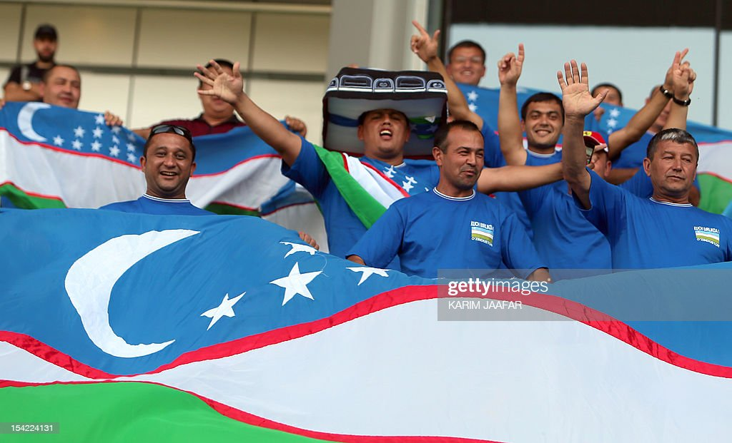 Uzbekistan fans hold up their national flag as they watch their national team play against Qatar during their group B 2014 World Cup Asian qualifying...