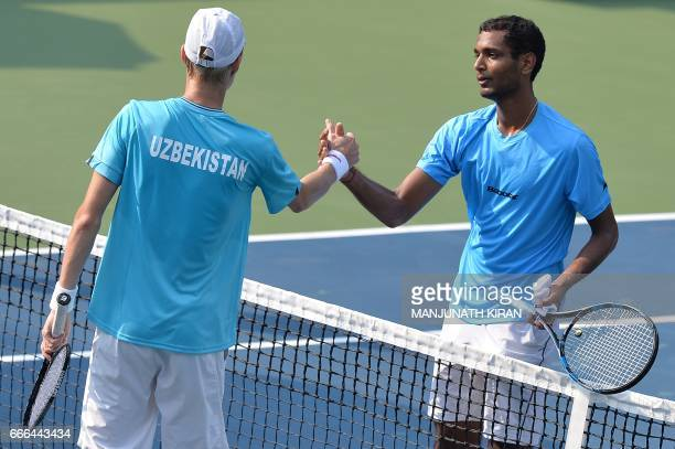 Uzbekistan player Sanjar Fayziev shakes hands with Indian player Ramkumar Ramanathan after the latter won their singles match at the Davis Cup Asia...