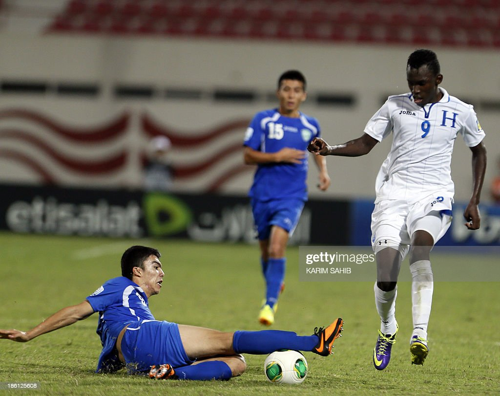 Uzbekistan's Akramio Komilov (L) tackles Honduras' Aiberth Elis (R) during their FIFA U-17 World Cup UAE 2013 football match, on October 28, 2013, at the Sharjah Stadium in Sharjah.