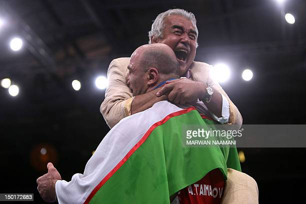 Uzbekistan's Artur Taymazov celebrates with coaches after defeating Georgia's Davit Modzmanashvili in their Men's 120kg gold medal match on August 11...