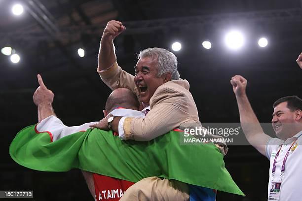 Uzbekistan's Artur Taymazov celebrates with coaches after defeating Georgia's Davit Modzmanashvili in their Men's 120kg gold medal match on August 11...