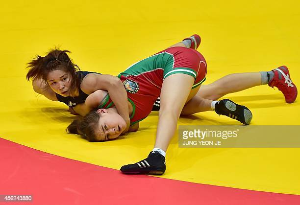 Uzbekistan's Asem Seydametove competes with Kazakhstan's Aiym Abdildina in the women's freestyle 55 kg qualification wrestling match during the 2014...