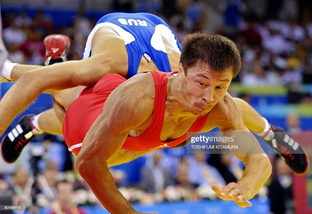 Uzbekistan's Dilshod Mansurov (red) is wrestled by Russia's Besik Kudukhov (red) during their 2008 Beijing Olympic Games wrestling men's 55kg freestyle bronze medal contest at the China Agricultural University Gymnasium in Beijing on August 19, 2008. Kudukhov won the match.