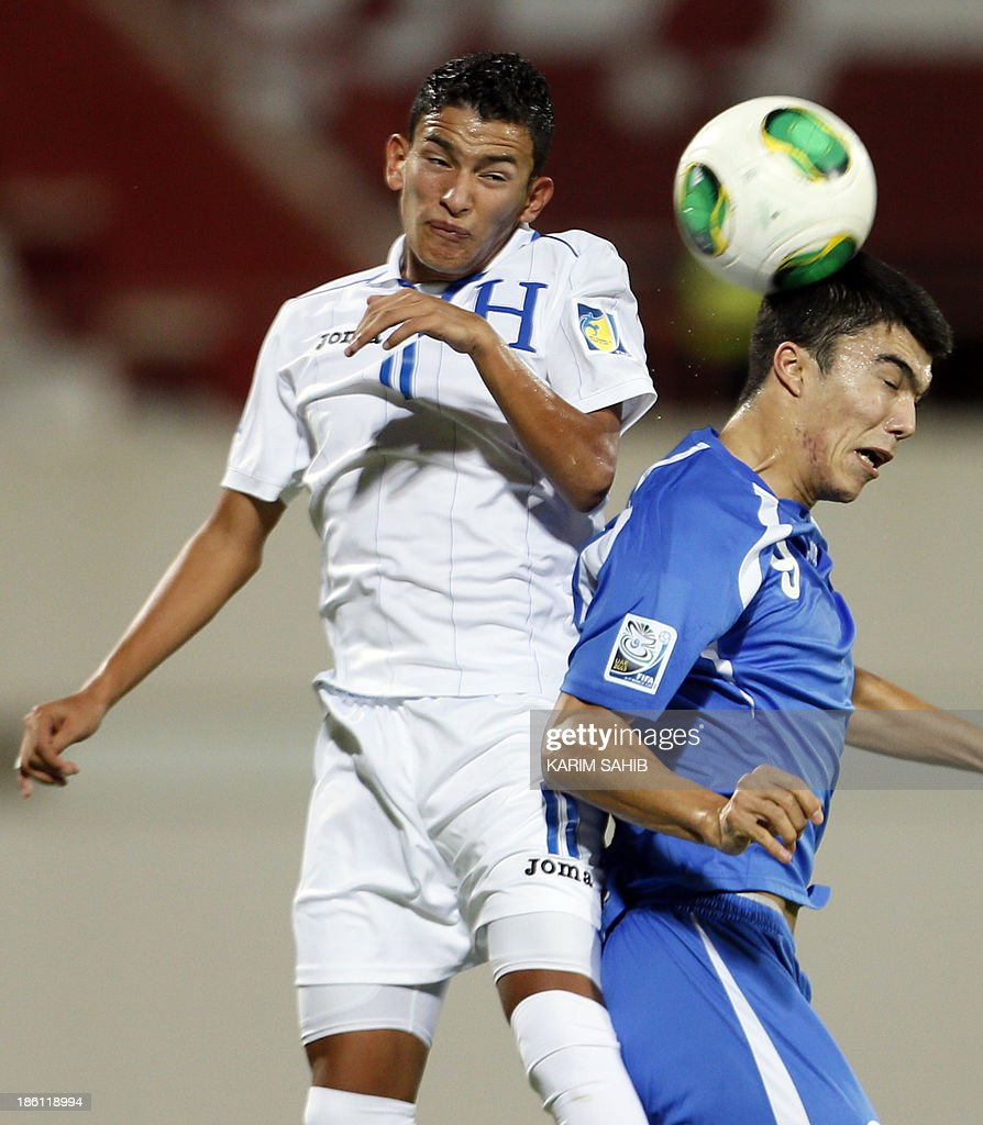 Uzbekistan's Ibrokhim Abdullaev (R) vies for the ball against Honduras's Rembrandt Flores (L) during their FIFA U-17 World Cup UAE 2013 football match on October 28, 2013, at the Sharjah Stadium in Sharjah.