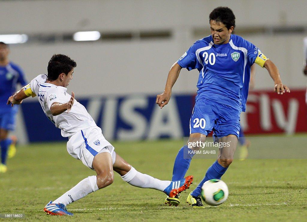 Uzbekistan's Otabek Shukurov (R) vies for the ball against Honduras's Luis Santos (L) during their FIFA U-17 World Cup UAE 2013 football match on October 28, 2013, at the Sharjah Stadium in Sharjah.