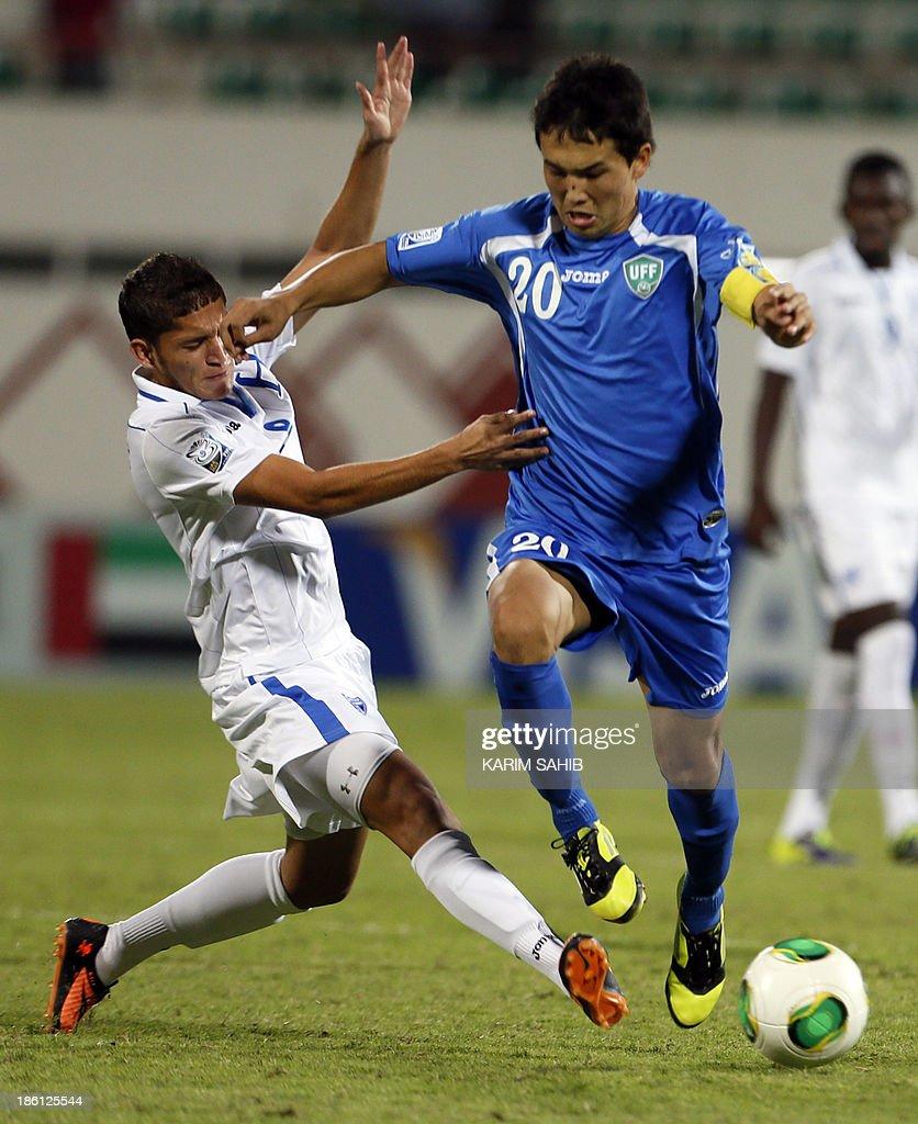 Uzbekistan's Otabek Shukurov (R) vies with Honduras' Christopher Alegria (L) during the FIFA U-17 World Cup UAE 2013 football match on October 28, 2013, at the Sharjah Stadium in Sharjah. Honduras won the match 1-0. AFP PHOTO/KARIM SAHIB