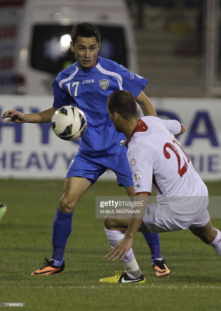 Uzbekistan's Sanjar Tursunov (back) challenges Jordan's Mohammed al-Dumeiri for the ball during their 2014 World Cup qualifier football match at the King Abdullah international stadium in Amman on September 6, 2012. The match ended in a draw. AFP PHOTO/KHALIL MAZRAAWI