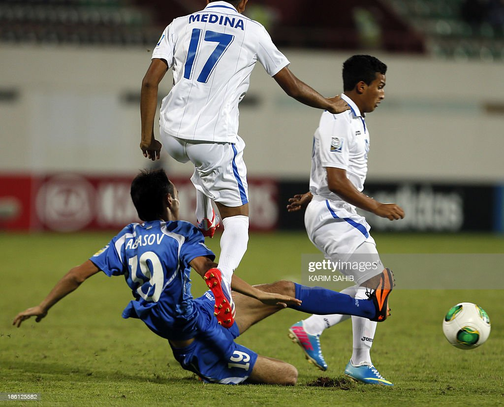 Uzbekistan's Shohjhon Abbasov (C) vies with Honduras' Fredy Medina (17) during their FIFA U-17 World Cup UAE 2013 football match on October 28, 2013, at the Sharjah Stadium in Sharjah. Honduras won the match 1-0.
