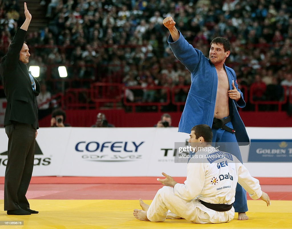 Uzbekistan's Yakhyo Imamov (blue) celebrates after beating Georgia's Avtandil Tchrikishvili (white) during the Men -81kg contest final match of the Paris' Judo Grand Slam tournament on february 10, 2013 in Paris. AFP PHOTO / JACQUES DEMARTHON