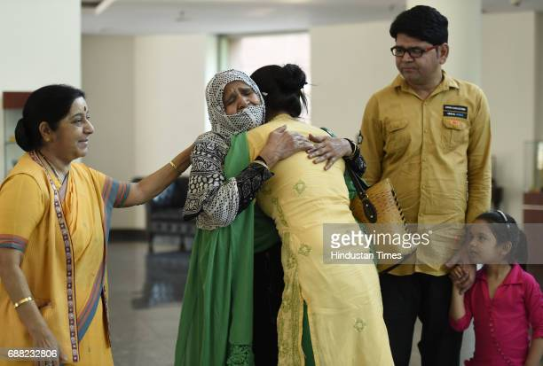 Uzma Ahmed hugs her mother as Union External Affairs Minister Sushma Swaraj her brother and daughter look on at Jawahar Bhawan after returning from...