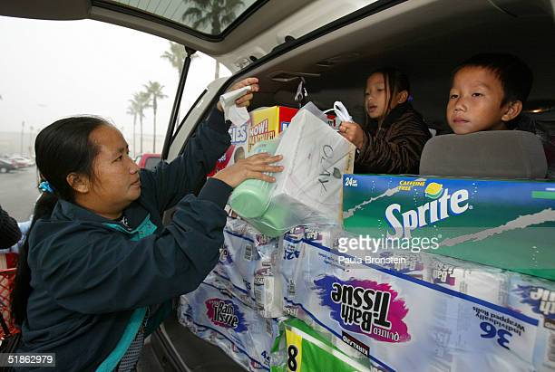 Va Vang loads up her sister's car with groceries as her children PaMee and Pa Choua sit in the back seat after shopping at Costco's supermarket...