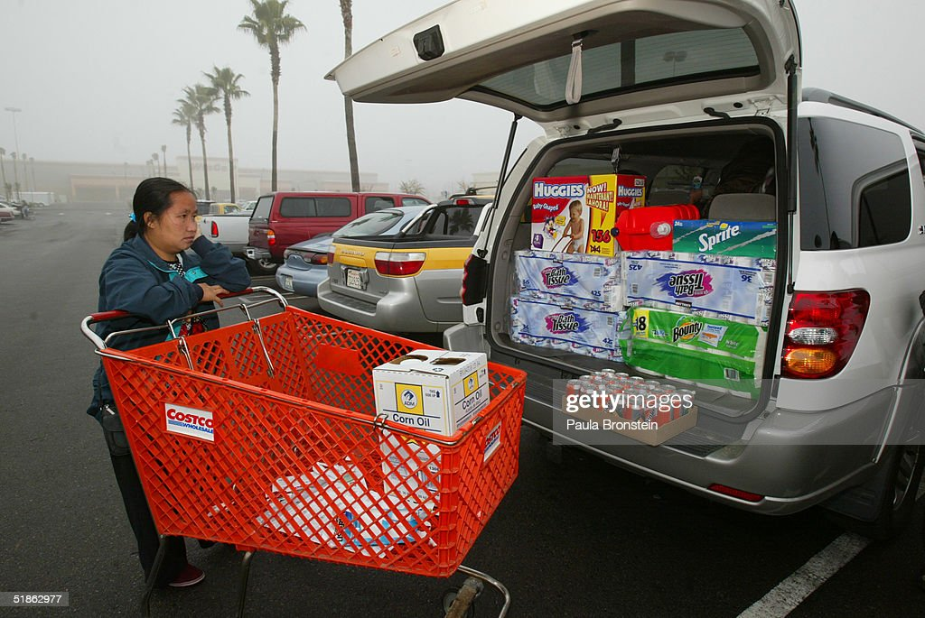 Va Vang stands by her sister's car after loading it up with goods after shopping at Costco supermarket December 112004 in Fresno California The Vang...