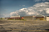 An empty, vacant commercial store with overgrown weeds and empty parking lot in the foreground.