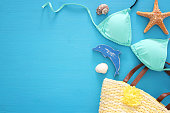 vacation and summer image with sea life style objects and mint bikini over blue wooden background