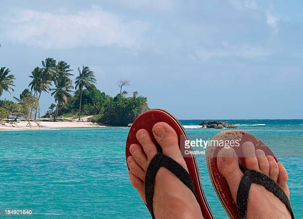 Vacation concept, feet against the view of small tropical island