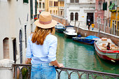 Rear view shot of a woman standing at canal in Venice while on sightseeing tour.