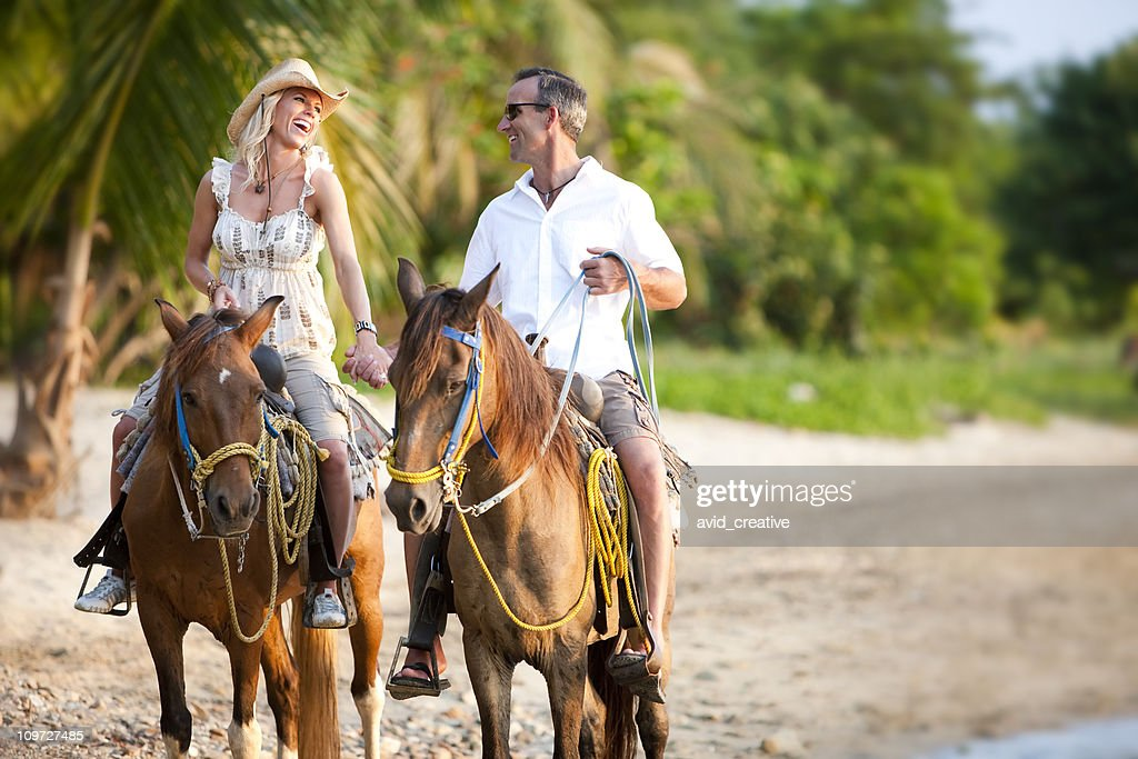 Vacation Lifestyles-Couple Riding Horses on Beach at Sunset