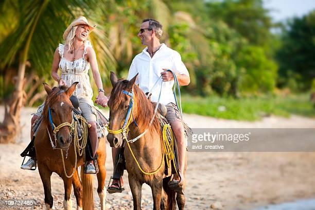 Vacances de style de vie-Couple équitation sur la plage au coucher du soleil