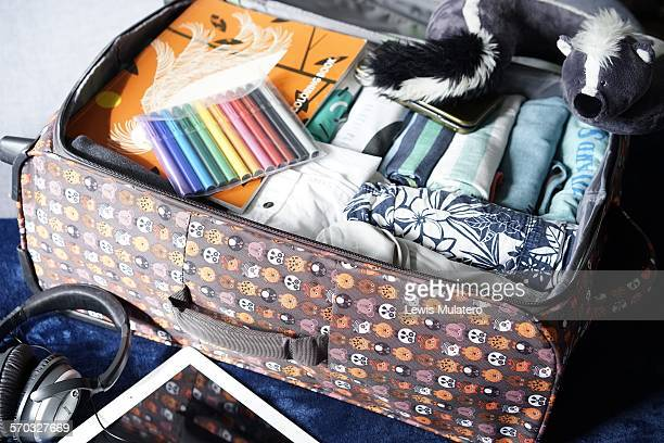 Vacation packing Suitcase neatly packed on bed of pre teenage boys summer clothes coloring book pens electronic game iPad headphones and fluffy toy...