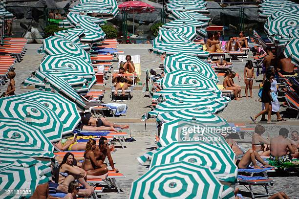 Vacationers sunbathe at a private beach near Santa Margherita Ligure southern Genova on August 11 2011 The highpeak tourism season has been slightly...