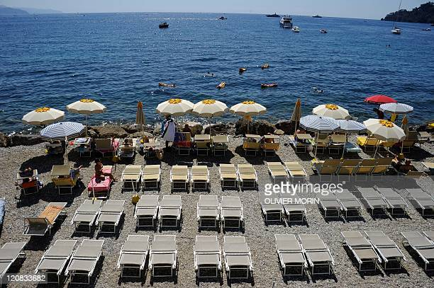 Vacationers swim and sunbathe at a private beach near Santa Margherita Ligure southern Genova on August 11 2011 The highpeak tourism season has been...