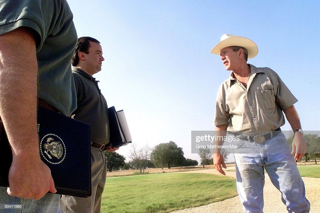 Vacationing President George W Bush talking w senior staff members Steve Biegun and press secretary Scott McClellan at the Bush Ranch