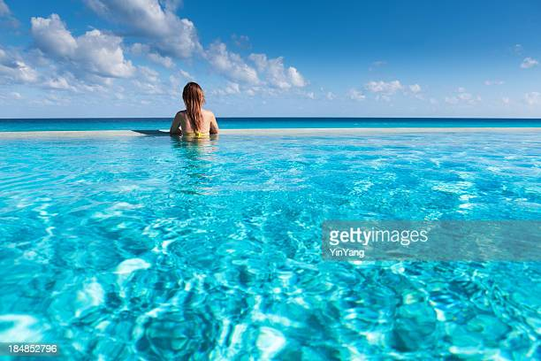 Vacationing Woman Enjoying Infinity Pool in Caribbean Beach Resort Hotel