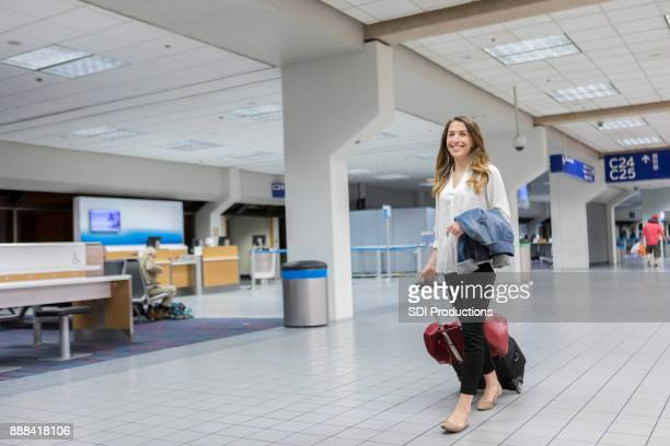 Vacationing young woman walks to airport gate